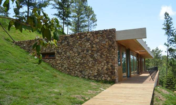 Grass Roofed Home Built Into Slope Uses Hillside Cooling