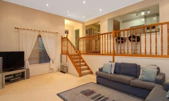 Split Level Living Room Using Beige Colours Carpet Staircase